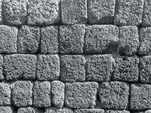 Monochrome picture of rough ancient stone wall in the sunlight Stock Images