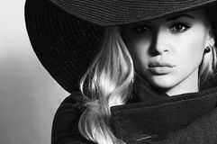 Monochrome portrait of Beautiful Blond Woman in Black Hat. Fashionable Lady in Topcoat