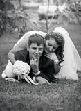 Monochrome portrait of bride and groom lying on grass Stock Photos