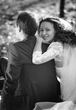 Monochrome portrait of cute smiling bride hugging grooms back wh Royalty Free Stock Photo