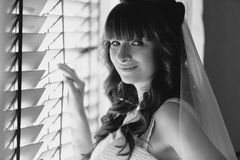Monochrome portrait of cute smiling bride standing at window Stock Photography