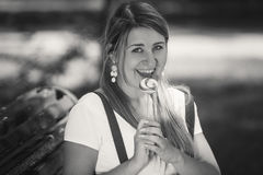 Monochrome portrait of cute woman licking lollipop at park Royalty Free Stock Photography