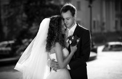 Monochrome portrait of embracing bride and groom on street Royalty Free Stock Photo