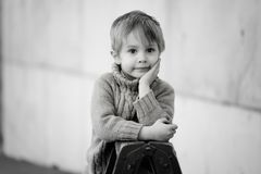 A four years old  blond, pensive  boy with a lovely eyes. A monochrome portrait of handsome boy wearing turtleneck, in head leaning hand, looking ahead, waist up Royalty Free Stock Image