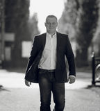 Monochrome portrait of handsome man in suit walking on street Stock Photography