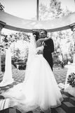 Monochrome portrait of happy bride and groom kissing at alcove Royalty Free Stock Photography