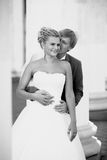 Monochrome portrait of happy bride and groom kissing at alcove Royalty Free Stock Photos