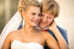 Monochrome portrait of happy bride and groom kissing at alcove Stock Photography