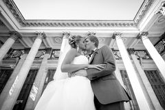 Monochrome portrait of just married couple kissing against class Stock Photo