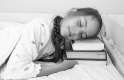 Monochrome portrait of little girl sleeping on pile of books at Royalty Free Stock Images