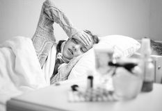Monochrome portrait of little sick girl lying at bed Stock Photography