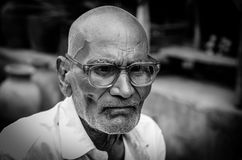 Monochrome portrait of an old Indian man siting at a bus stand i Royalty Free Stock Photo