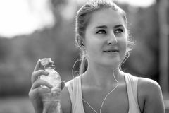 Monochrome portrait of sexy sporty woman with bottle of water at Royalty Free Stock Photo