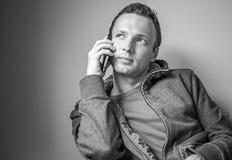 Monochrome portrait of sitting man talking on cell phone Stock Photo