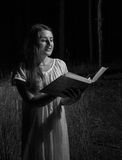 Monochrome portrait of woman holding big old book at night fores Stock Photography