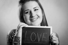 Monochrome portrait of woman posing with blackboard with word love Stock Photography