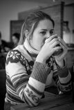 Monochrome portrait of woman in sweater drinking coffee at cafe Royalty Free Stock Photos