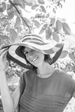 Monochrome portrait of a woman in a wide brimmed sunhat looking. Monochrome portrait of a woman in a wide brimmed sunhat standing outdoors looking to the camera royalty free stock photos