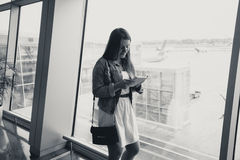 Monochrome portrait of young woman using digital tablet at airpo Royalty Free Stock Photos