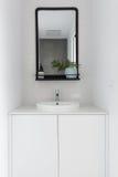 Monochrome powder room vanity black mirror and white tiling. Monochrome powder room vanity and black mirror and white tiling royalty free stock image