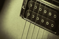 Monochrome retro image of a guitar pickup. Black humbucker pickup on a gold guitar. Retro monochrome image with a soft feel. Nice background or poster image for Stock Photography