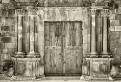 Free Monochrome Sepia Ancient Wooden Double Doors In An Old Stone Building With Crumbling Ornate Columns Surrounding The Entrance Stock Images - 147960314