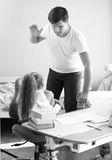 Monochrome shot of angry father hitting intimidated daughter. Black and white shot of angry father hitting intimidated daughter Stock Images