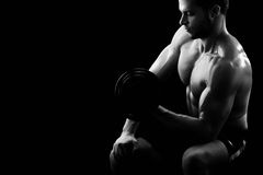 Monochrome shot of an athletic ripped young sportsman with dumbb. Black and white horizontal cropped shot of a focused young athletic man with muscular strong Royalty Free Stock Photo