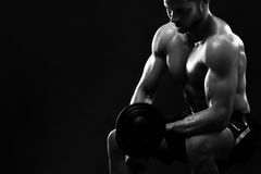 Monochrome shot of an athletic ripped young sportsman with dumbb. Black and white shot of a strong young muscular athlete exercising with dumbbells strengthening Royalty Free Stock Photos