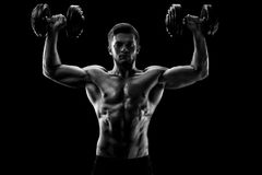 Monochrome shot of an athletic ripped young sportsman with dumbb. Black and white studio shot of a handsome young shirtless weightlifter exercising with Stock Photography