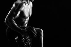 Monochrome shot of an athletic ripped young sportsman with dumbb. Cropped monochrome close up of a ripped athletic man exercising with dumbbells copyspace Stock Image