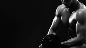Monochrome shot of an athletic ripped young sportsman with dumbb Stock Image