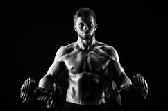 Monochrome shot of an athletic ripped young sportsman with dumbb. Monochrome portrait of a shirtless muscular young male bodybuilder training with weights epic Royalty Free Stock Images