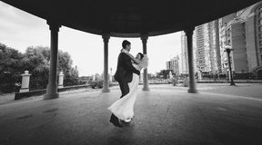 Monochrome shot of bride and groom dancing at alcove in park Royalty Free Stock Images