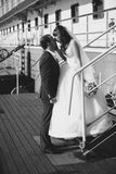 Monochrome shot of bride and groom kissing on pier against cruis Stock Image