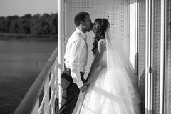 Monochrome shot of bride and groom kissing on ship deck Royalty Free Stock Photography