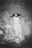 Monochrome shot of woman in white dress swimming at pool Royalty Free Stock Image