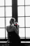 Monochrome silhouette image of young woman standing in her apartment sipping a glass of red wine , side view at window Royalty Free Stock Photo