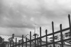 Monochrome spire of Catholic church with cross and wrought fence. Monochrome image of spire of the Catholic church with a cross on a background of cloudy sky. In Royalty Free Stock Images