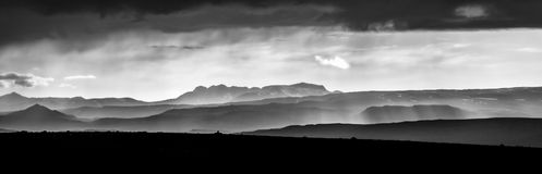 Monochrome sunset over mountains. Fantastic panorama view of misty layered icelandic landscape with dramatic clouds. Monochromatic sunlight sunset with layered stock photos