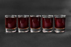 Summer cocktail on isolated black background. Monochrome transparent cocktails, a set of shots in one row, five servings, with taste of berries, cherries Stock Image