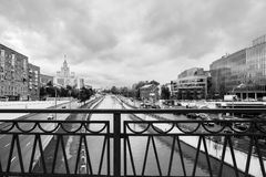 Monochrome urban landscape on rainy day. View of the river Yauza through the bridge Visokoyauzskiy, Moscow, Russia. View of the river Yauza and roadways of its stock photos