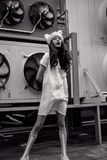 Monochrome urban teenager in white dress and fur hat Royalty Free Stock Photography