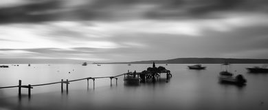 Monochrome view of a pier and boats over sea taken with long exposure Royalty Free Stock Photo