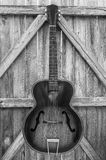 Monochrome Vintage Acoustic Guitar On Fence Stock Images