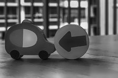 Monochrome Wooden toy cars with arrow on the circle on the table.  Royalty Free Stock Photo