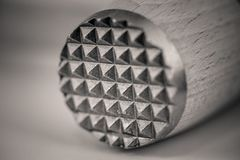 Monocrome macro shot of a wooden meat tenderizer, metal end royalty free stock photos