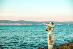Monocular mirando el paisaje del mar de la tarde imágenes de archivo libres de regalías
