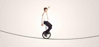 Monocycle extrême d'équitation d'homme d'affaires sur une corde Photographie stock