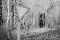 Monohrom Het oude, rachitische teken geeft tegen het snow-covered bos en het gebied uiting Verkeersteken, regels van de weg Witte stock afbeelding